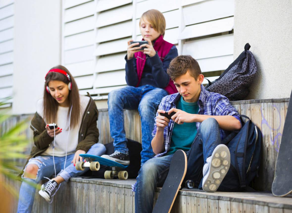 Three teenagers with smartphones by verkeorg
